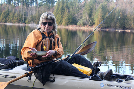 Photo of kayak fishing guide Howard Zatwarnitski sitting on his kayak with a fresh-caught fish in his hands