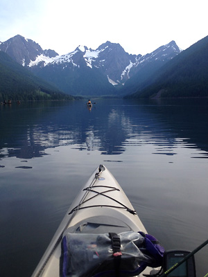 Beautiful photo of a kayak fishing in the foreground with calm water and gorgeous mountains reflected in the distance