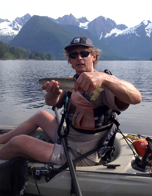 Photo of kayak fishing guide holding up his catch