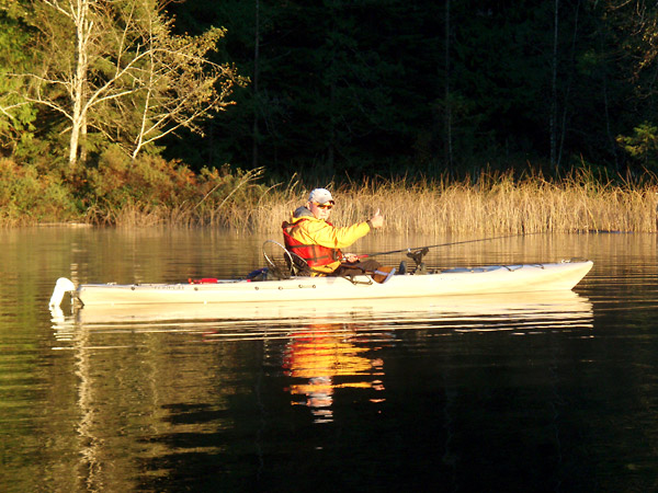 Photo of a fisherman sitting in his kayak fishing