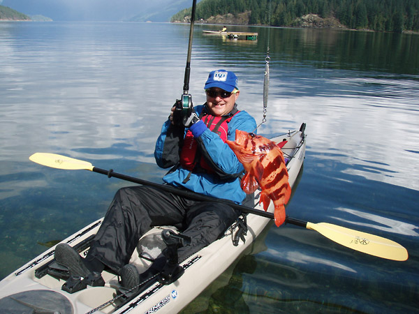 Photo of a kayak ocean kayak fishing tour participant holding up his catch