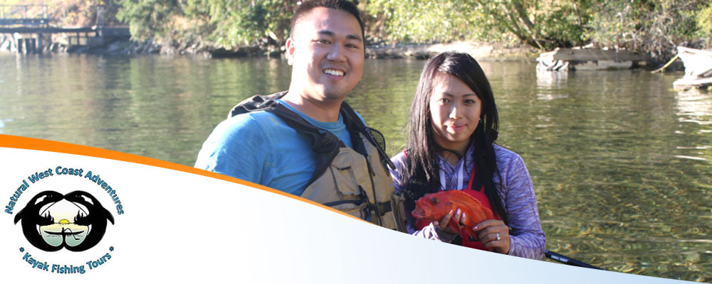 Photo of a smiling young Asian couple enjoying kayak fishing